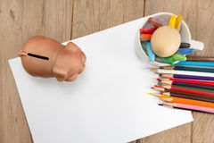 Crayons and piggy bank on a sheet of paper Stock Photos