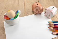 Crayons and piggy bank on a sheet of paper Stock Images