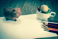 Crayons and piggy bank on a sheet of paper,vintage effect filter Stock Photos