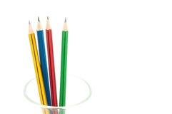 4 crayons pointus de couleur se ferment dans un verre sur le fond blanc Photographie stock