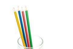 4 crayons pointus de couleur se ferment dans un verre sur le fond blanc Photos stock