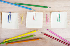 Crayons, post-it, and paperclips Stock Photos