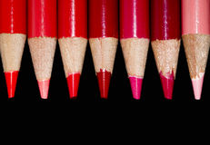 7 crayons rouges - fond noir Photographie stock
