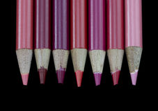 7 crayons rouges - fond noir Photos stock