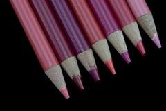 7 crayons rouges - fond noir Photographie stock libre de droits