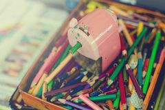 Crayons and sharpener in the box Royalty Free Stock Photo