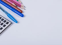 Crayons, stylos et une calculatrice sur un fond blanc Non d'isolement Photographie stock libre de droits