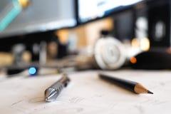 Crayons sur un bureau, près des moniteurs d'ordinateur et d'un croquis Images libres de droits