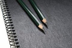 Crayons verts s'étendant sur une reliure à anneaux noire Photographie stock libre de droits
