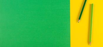 Crayons verts sur le fond vert et jaune en pastel de contraste concept créatif minimal Photos stock