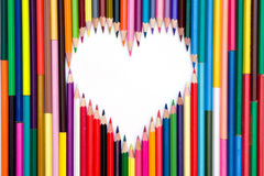 Crayons with white heart. A lot of colorful crayons and the white heart royalty free stock images