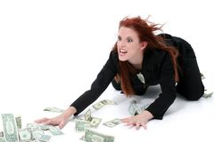 Crazed Business Woman Grabbing Money From Floor. Very funny expression on model's face. Shot in studio over white stock photography