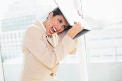 Crazed slå för affärskvinna head av bärbara datorn Royaltyfri Foto