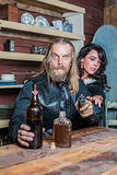 Crazed Western Man With Woman at Table. Crazed Western Man Aims Gun Towards You as he Sits at Table With Woman Royalty Free Stock Photos