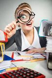 Crazy bizarre businesswoman with big loupe. Royalty Free Stock Photography