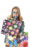 Crazy amusing young girl with shopping gift bags in the teeth. Crazy amusing young girl with shopping gift bags in the teeth, wearing creative blue glasses on royalty free stock photos