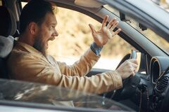 Free Crazy Angry Man Annoyed While Driving A Car. Mad Agrressive Driver Screaming Irritated With Traffic Royalty Free Stock Image - 176284076
