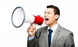Crazy Asian businessman screaming in megaphone on white backgrou Stock Photos
