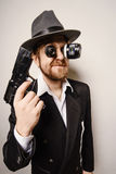 Crazy beard detective whit gun in hat Stock Image