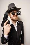 Crazy beard detective whit gun in hat Stock Image