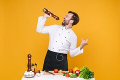 Crazy bearded male chef cook or baker man in white uniform isolated on yellow background. Cooking food concept. Mock up