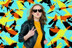 Crazy beautiful rock Girl in leather jacket and black sunglasses. Punk is not dead. Attractive cool young woman blowing a kiss. Crazy beautiful rock Girl in Stock Images