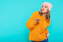 Crazy beautiful trendy girl in colorful clothes and pink beanie hat blowing a kiss. Attractive cool young woman portrait. Royalty Free Stock Image