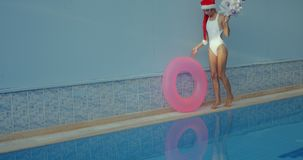 Beautiful young woman in Santa hat near swimming pool. Crazy beautiful young woman in Santa hat with Christmas tree pushing inflatable ring along the swimming stock video footage