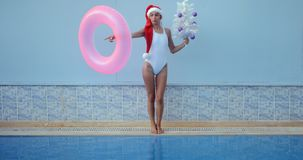 Beautiful young woman in Santa hat near swimming pool. Crazy beautiful young woman in Santa hat funny moving with inflatable ring and Christmas tree by the stock video footage