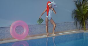 Beautiful young woman in Santa hat near swimming pool. Crazy beautiful young woman in Santa hat funny walking with present and Christmas tree by the swimming stock video