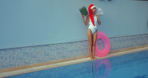 Beautiful young woman in Santa hat near swimming pool. Crazy beautiful young woman in Santa hat with present and Christmas tree pushing inflatable ring along the stock footage