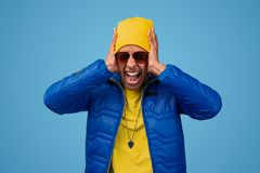 Crazy black man screaming and covering ears. Mad African american male in stylish urban outfit covering ears and shouting in shock while standing against blue royalty free stock photo