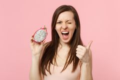 Crazy blinking young woman showing thumb up, holding half of fresh ripe pitahaya, dragon fruit isolated on pink pastel. Background. People vivid lifestyle relax stock photography