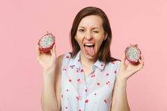 Crazy blinking young woman showing tongue holding halfs of fresh ripe pitahaya, dragon fruit isolated on pink pastel. Wall background. People vivid lifestyle royalty free stock image