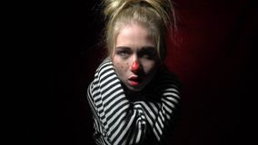 Mad woman clown choking herself and laughing. Crazy blonde in a clown makeup suffocates herself stock video