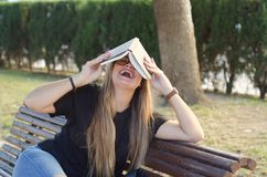Crazy blonde girl with glasses holding a book in the head royalty free stock images