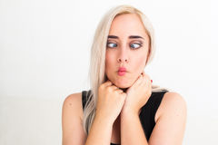 Crazy blonde woman makes squint for fun Royalty Free Stock Photography