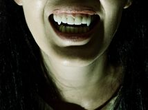 Crazy bloody scary vampire girl with fangs stock photography
