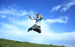 Crazy boy. Young happy boy jumping on a grass Royalty Free Stock Photography