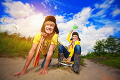 Crazy boy and girl are sledding at summer Stock Photography