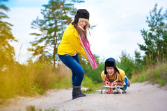 Crazy boy and girl are sledding at summer Royalty Free Stock Images