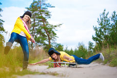 Crazy boy and girl are sledding at summer Stock Image