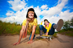 Crazy boy and girl are sledding at summer Stock Images