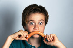 Crazy boy. Making moustache with sausage Stock Photo