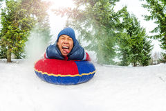Crazy boy on snow tube in winter fir forest Stock Photo