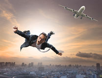 Crazy business man flying from passenger plane with glad and hap Stock Image