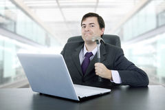 Crazy business man. Young crazy businessman with a hammer smashing a laptop, at the office Stock Image