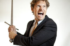 Crazy businessman attacking with a sword Royalty Free Stock Image