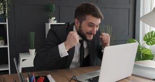Crazy businessman celebrating online success. Excited businessman cheering and celebrating success using laptop at office desk stock video