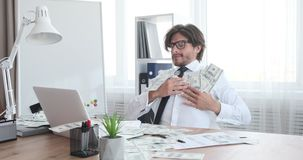 Crazy businessman celebrating success with cash dollars. Crazy businessman throwing cash dollars and celebrating success at office stock footage